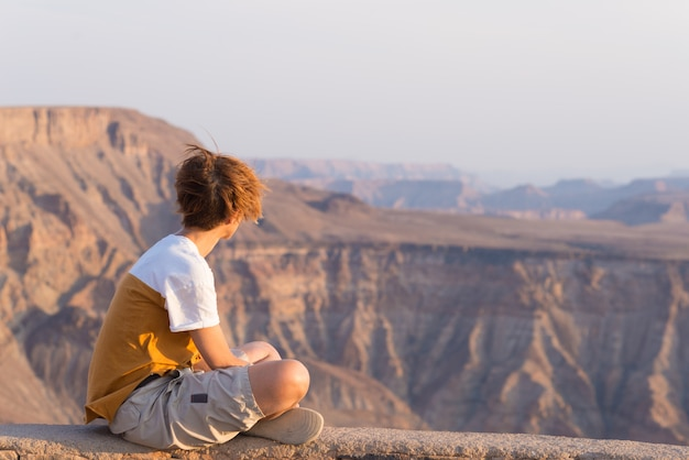 Una persona che guarda il fish river canyon, destinazione scenica di viaggio nel sud della namibia. ampia vista al tramonto. wanderlust viaggiando persone.