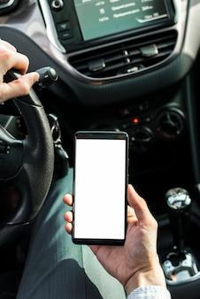 Una persona che guida l'automobile tenendo il telefono cellulare con schermo bianco