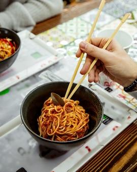 Una persona che mangia gli spaghetti al pomodoro con bastoncini