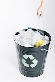 Una persona che mette la spazzatura nel secchio di riciclaggio su sfondo bianco