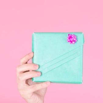 Una persona che mostra il contenitore di regalo turchese avvolto su sfondo rosa