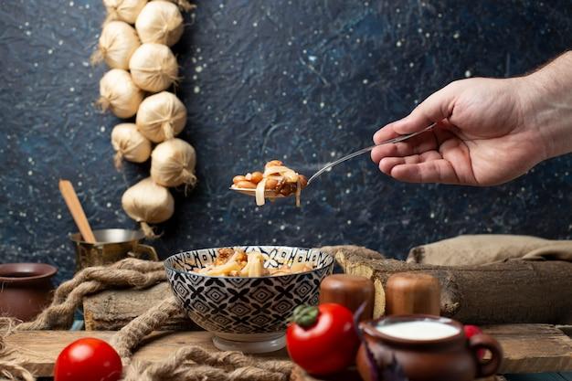 Una persona che prende la tagliatella di fagioli dalla ciotola con il cucchiaio.
