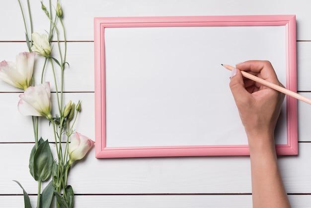 Una persona che scrive sul bordo bianco in bianco con la matita contro il contesto in legno