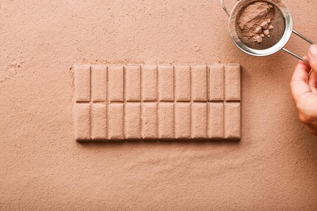 Una persona che spolvera la polvere di cacao dal setaccio sulla tavoletta di cioccolato