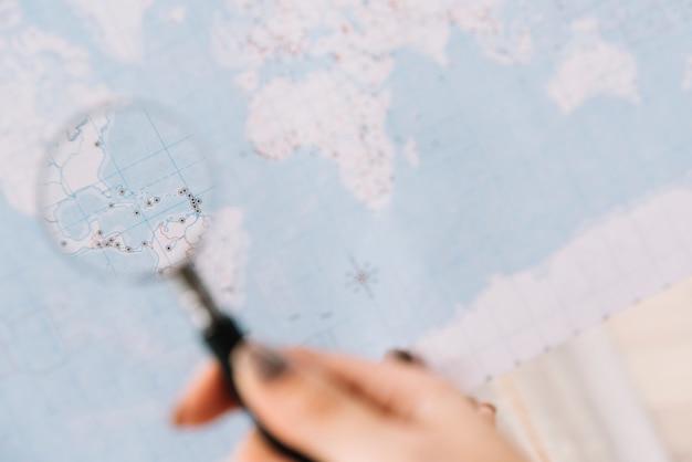 Una persona che tiene la lente di ingrandimento sulla mappa alla ricerca di destinazione