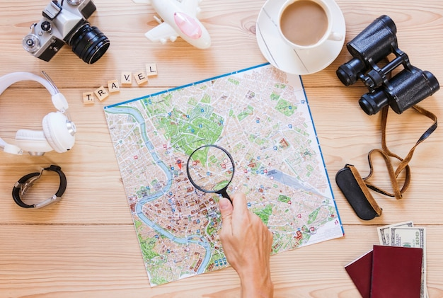 Una persona che tiene la lente di ingrandimento sulla mappa con la tazza di tè e attrezzature da viaggio sulla scrivania in legno