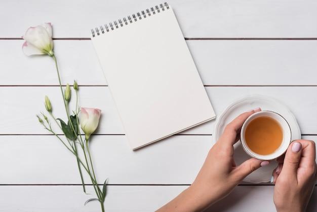 Una persona che tiene la tazza di tè con blocco note a spirale e bellissimi fiori sulla scrivania in legno