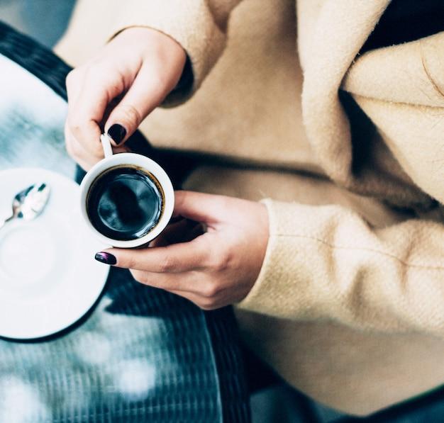 Una persona in possesso di una tazza di caffè