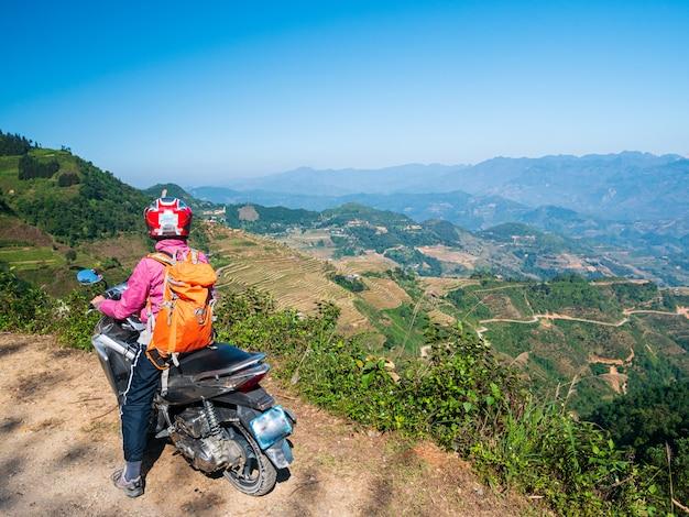 Una persona in sella a una bicicletta sul circuito di ha giang, famosi ciclisti di destinazione di viaggio, motociclisti facili. paesaggio della montagna del geopark di morfologia carsica di ha giang nel vietnam del nord. strada tortuosa in uno scenario mozzafiato.