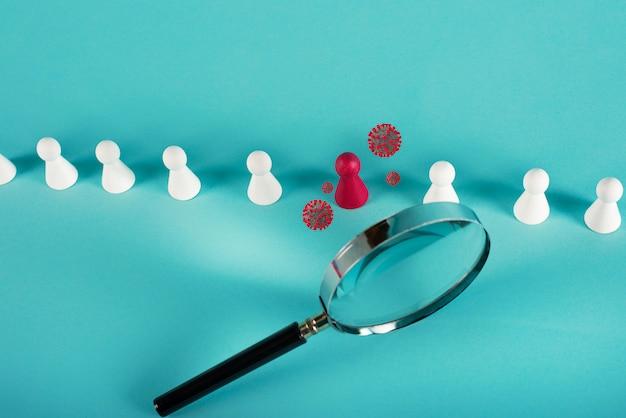 Una persona infetta di coronavirus covid-19 è stata trovata da una lente di ingrandimento. sfondo ciano