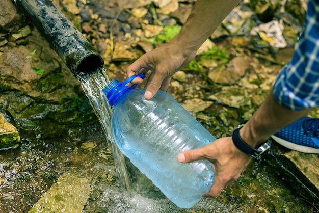 Una persona raccoglie acqua pulita da una sorgente in una bottiglia di plastica