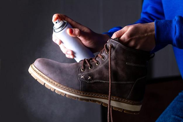Una persona sta pulendo e spruzzando l'agente sugli stivali casual in pelle scamosciata da uomo per proteggerlo dall'umidità e dallo sporco. lustrascarpe