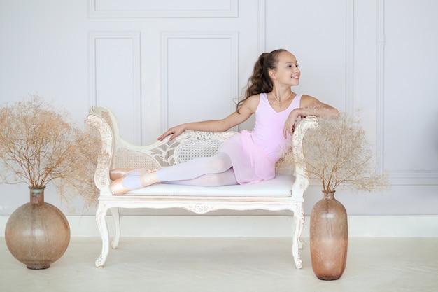 Una piccola ballerina carina con un costume da balletto rosa e le punte si siede sul divano.