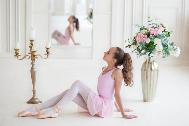 Una piccola ballerina carina in un costume da balletto rosa e punte seduto sul pavimento. ballerina nella classe di danza. la ragazza studia balletto.