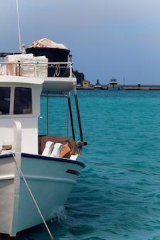 Una piccola barca da pesca legata nel porto su un bellissimo mare