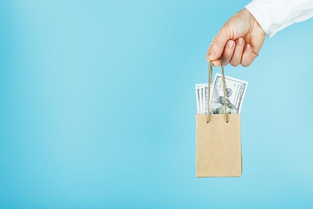 Una piccola borsa di carta in una mano tesa con dollari usa