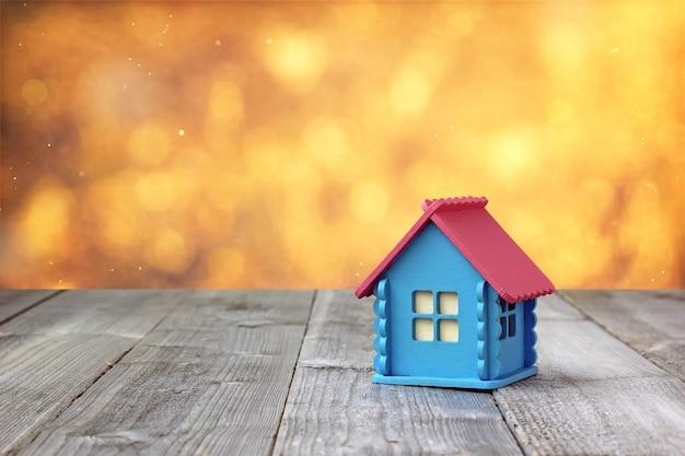 Una piccola casa di legno con pareti blu e tetto rosa sul tavolo