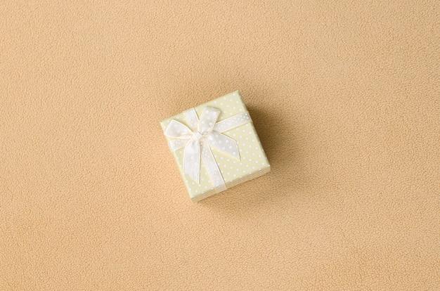 Una piccola confezione regalo in arancione con un piccolo fiocco si trova su una coperta di morbido e felpato tessuto in pile arancione chiaro.