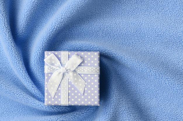 Una piccola confezione regalo in blu con un piccolo fiocco si trova su una coperta di morbido e felpato tessuto felpato blu chiaro con molte pieghe in rilievo.