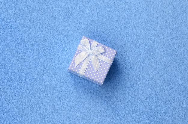 Una piccola confezione regalo in blu con un piccolo fiocco si trova su una coperta di morbido tessuto felpato blu chiaro.