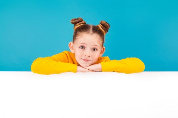 Una piccola ragazza carina che indossa una maglietta gialla