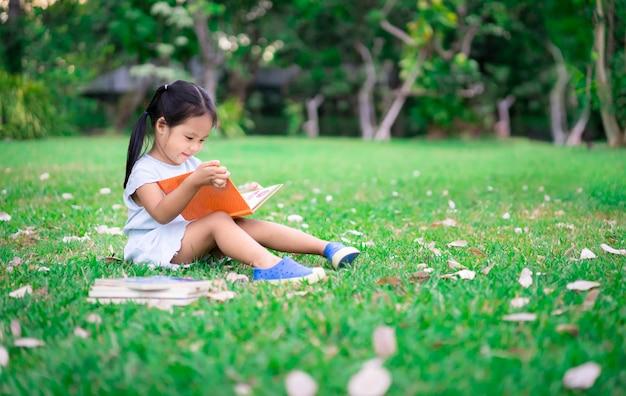 Una piccola ragazza carina in un abito blu, leggendo un libro seduto nel parco