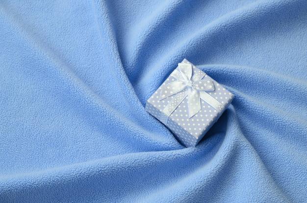 Una piccola scatola regalo in blu con un piccolo fiocco si trova su una coperta di morbido