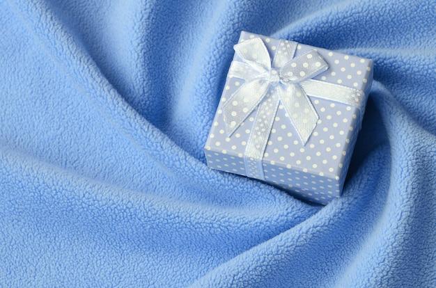 Una piccola scatola regalo in blu con un piccolo fiocco si trova su una coperta