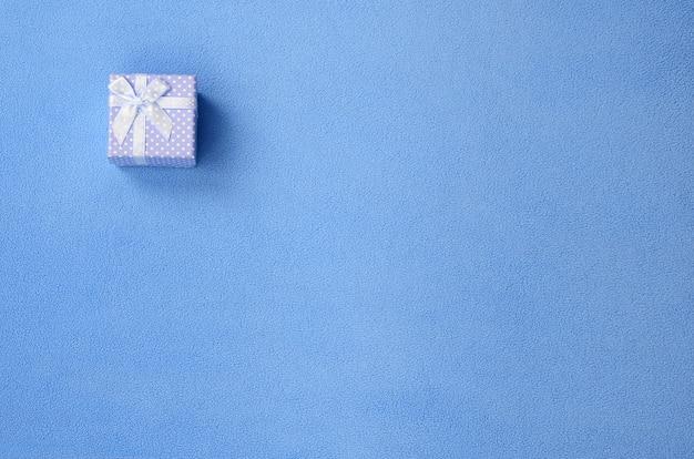 Una piccola scatola regalo in blu con un piccolo inchino
