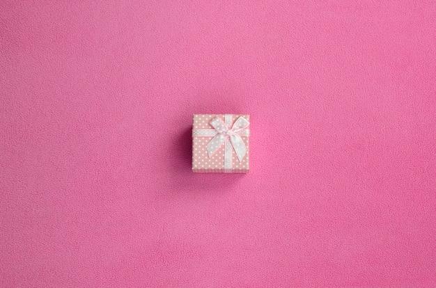 Una piccola scatola regalo in rosa con un piccolo fiocco si trova su una coperta di morbido e felpato tessuto rosa chiaro. imballaggio per un regalo alla tua adorabile fidanzata