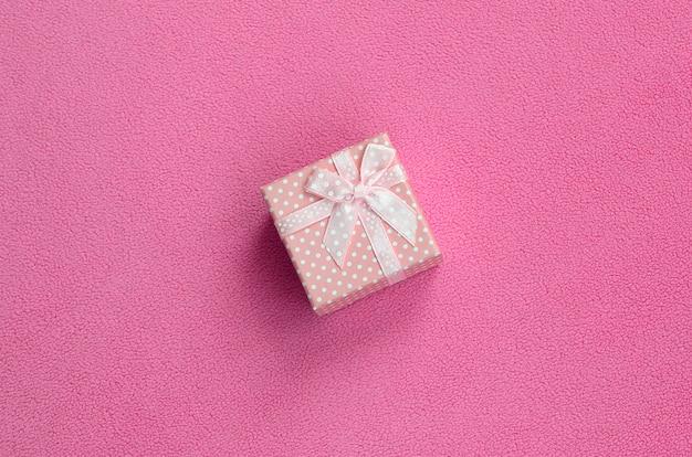Una piccola scatola regalo in rosa con un piccolo fiocco si trova su una coperta di morbido e felpato tessuto rosa chiaro