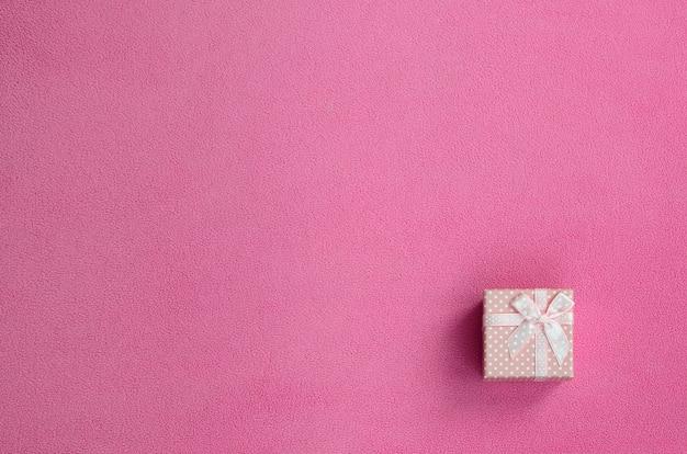 Una piccola scatola regalo in rosa con un piccolo fiocco si trova su una coperta di tessuto in pile