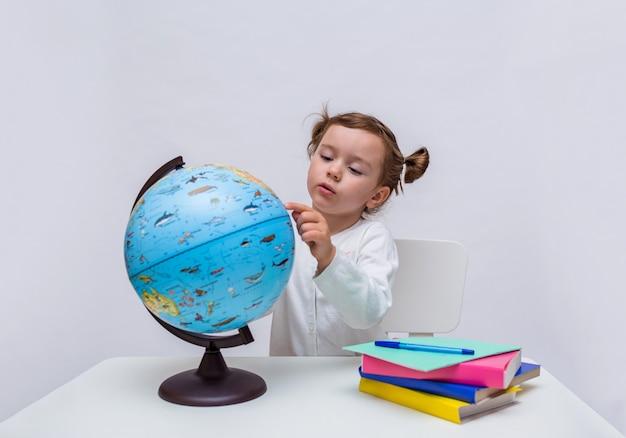 Una piccola studentessa si siede con un globo a un tavolo su uno sfondo bianco isolato
