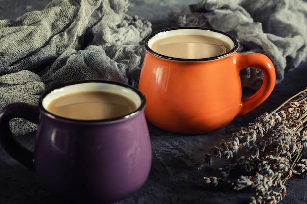Una piccola tazza arancione e viola con caffè caldo. vicino alla lavanda secca.