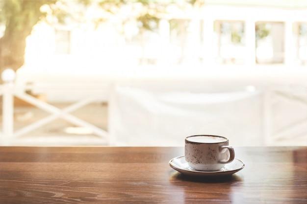Una piccola tazza di cappuccino su un tavolo vicino alla finestra.