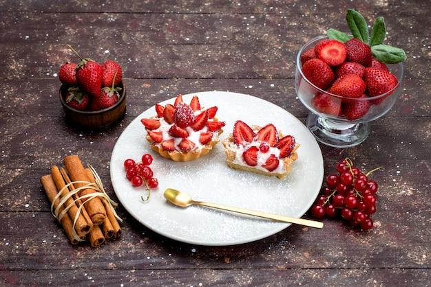 Una piccola torta di vista superiore con crema e fragole fresche affettate all'interno del piatto bianco insieme alla cannella sul tè marrone della torta della frutta dello scrittorio