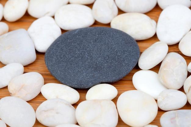 Una pietra nera e molte piccole pietre bianche