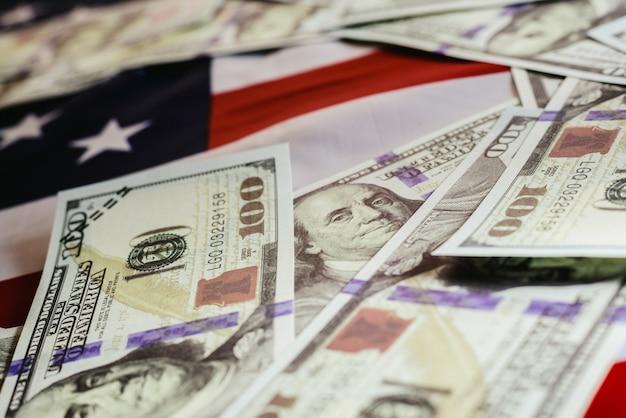 Una pila di 100 banconote in dollari sulla bandiera americana.
