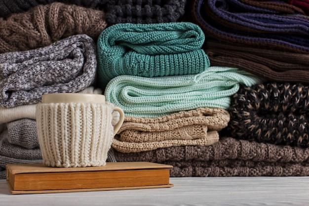 Una pila di abiti a maglia di diversi colori e trame, sul tavolo accanto a un libro e una tazza in una custodia