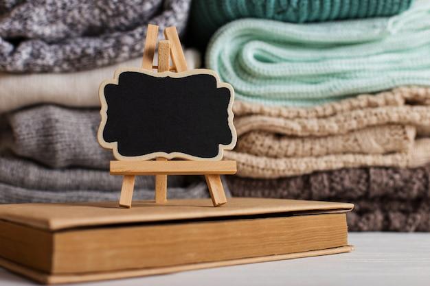 Una pila di abiti a maglia di diversi colori e trame, sul tavolo accanto a un libro