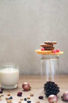 Una pila di biscotti al cioccolato su cialde croccanti e un bicchiere accanto a un bicchiere di latte e molte noci miste e uvetta, palline di natale e pigna sparse attorno ad esso sul tavolo di legno