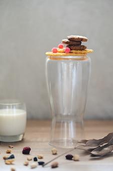 Una pila di biscotti al cioccolato su cialde croccanti e una brocca di vetro accanto a un bicchiere di latte e foglie marroni secche con rami, molte noci miste e uvetta sul tavolo di legno