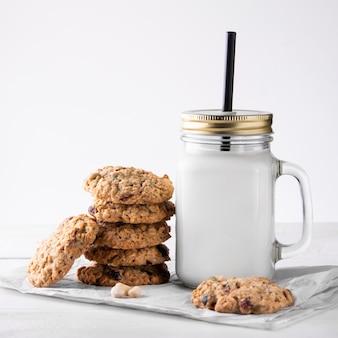 Una pila di biscotti di farina d'avena e una tazza di latte su una parete leggera. avvicinamento.