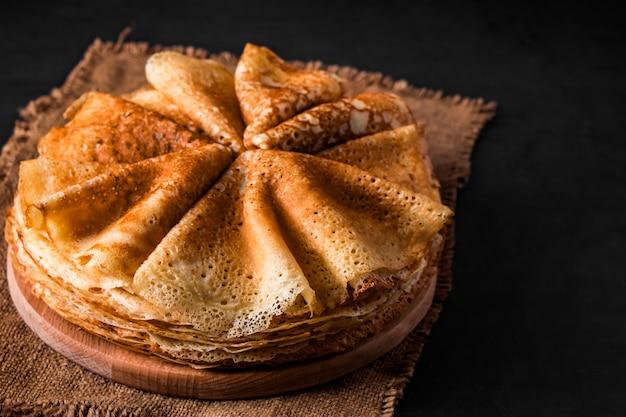 Una pila di deliziose frittelle su sfondo nero. cibo per le vacanze maslenitsa. posto per il tuo testo.