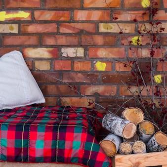 Una pila di legno di betulla vicino al divano con una coperta rossa sulla terrazza coperta di neve invernale aperta