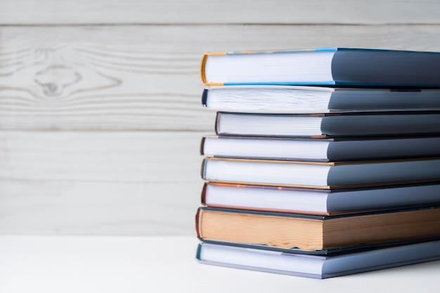 Una pila di libri che si trovano sul tavolo su uno sfondo in legno chiaro. di nuovo a scuola. educazione di base.