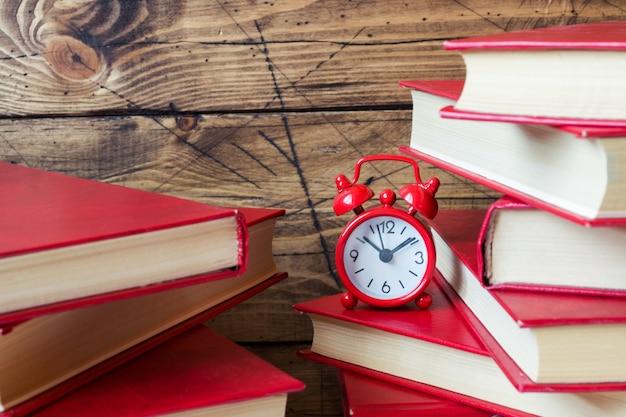 Una pila di libri con copertina rigida e una sveglia su un tavolo di legno. copia spazio per il testo