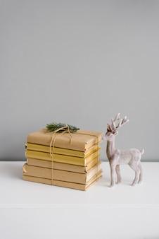 Una pila di libri e un rametto di abete rosso e accanto a una statuetta di un cervo