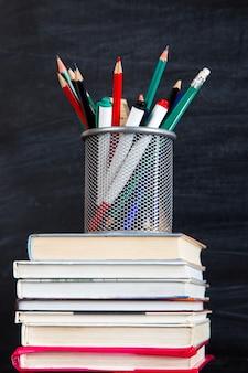 Una pila di libri, in cima allo stand con penne e matite, contro una lavagna nera, copia spazio.