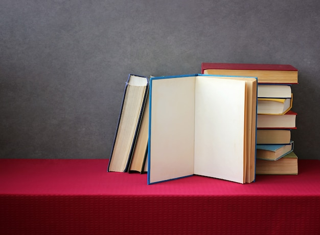 Una pila di libri nelle copertine colorate sul tavolo con una tovaglia rossa.